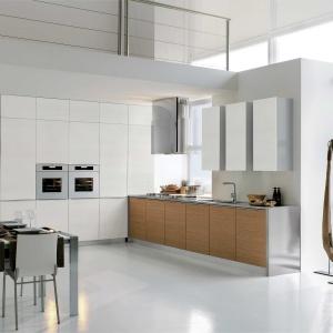 Ultra-nowoczesna kuchnia z bardzo wysoką białą zabudową, w której zaplanowano białe sprzęty AGD. Dolna zabudowa prostopadła do wysokiej zabudowy ma fronty z drewnianym dekorem. Fot. Stosa Cucine, kuchnie Diamente.