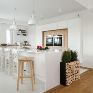 Piękna biała kuchnia, w której mocno zaznaczono obecność drewna. W ciepłym wybarwieniu i pionowym dekorze jest obecne na wysokiej zabudowie wokół sprzętów AGD, na granicy kuchni przyjęło formę otwartych pieńków. Fot. Pracownia Mebli Vigo.