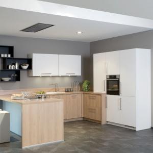 Fronty i blat dolnej zabudowy kuchennej zdobi drewniany dekor podczas gdy wysoka zabudowa oraz dwie szafki górne są w całości białe. Fot. Brigitte.