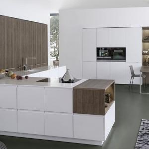 Nowoczesna kuchnia z dużym półwyspem i wysoką zabudową wpasowaną we wnękę w ścianie. Gładkie, białe fronty pozbawione uchwytów przełamano wstawkami w kolorze lekko popielatego drewna. Fot. Leicht, kuchnia Pur-FS | Topos.