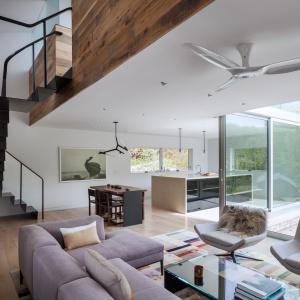 Białe ściany i przewaga szarości i jasnych kolorów drewna tworzą delikatną, subtelną aranżację, której mocniejszy charakter nadaje pomalowana na czarno stal w postaci np. schodów prowadzących na piętro. Projekt: Sharon Davis Design. Fot. Elizabeth Felicella