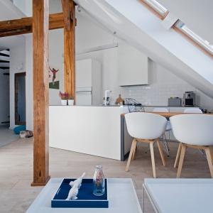 Otwartą strefę dzienną tworzą salon oraz kuchnia z wyspą, która przechodzi w jadalniany stół. Projekt: Superpozycja architekci. Fot. Przemek Skóra.