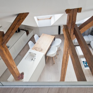 Antresolę zamyka od strony wysokiej strefy dziennej przeszklona ścianka, która pozwala obserwować z pozycji półpiętra, to co dzieje się w kuchni i salonie. Projekt: Superpozycja architekci. Fot. Przemek Skóra.