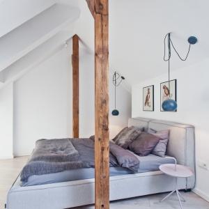 Na antresoli urządzono sypialnię, garderobę i schowek. Podwójne małżeńskie łoże z dwóch stron okalają drewniane belki. Projekt: Superpozycja architekci. Fot. Przemek Skóra.