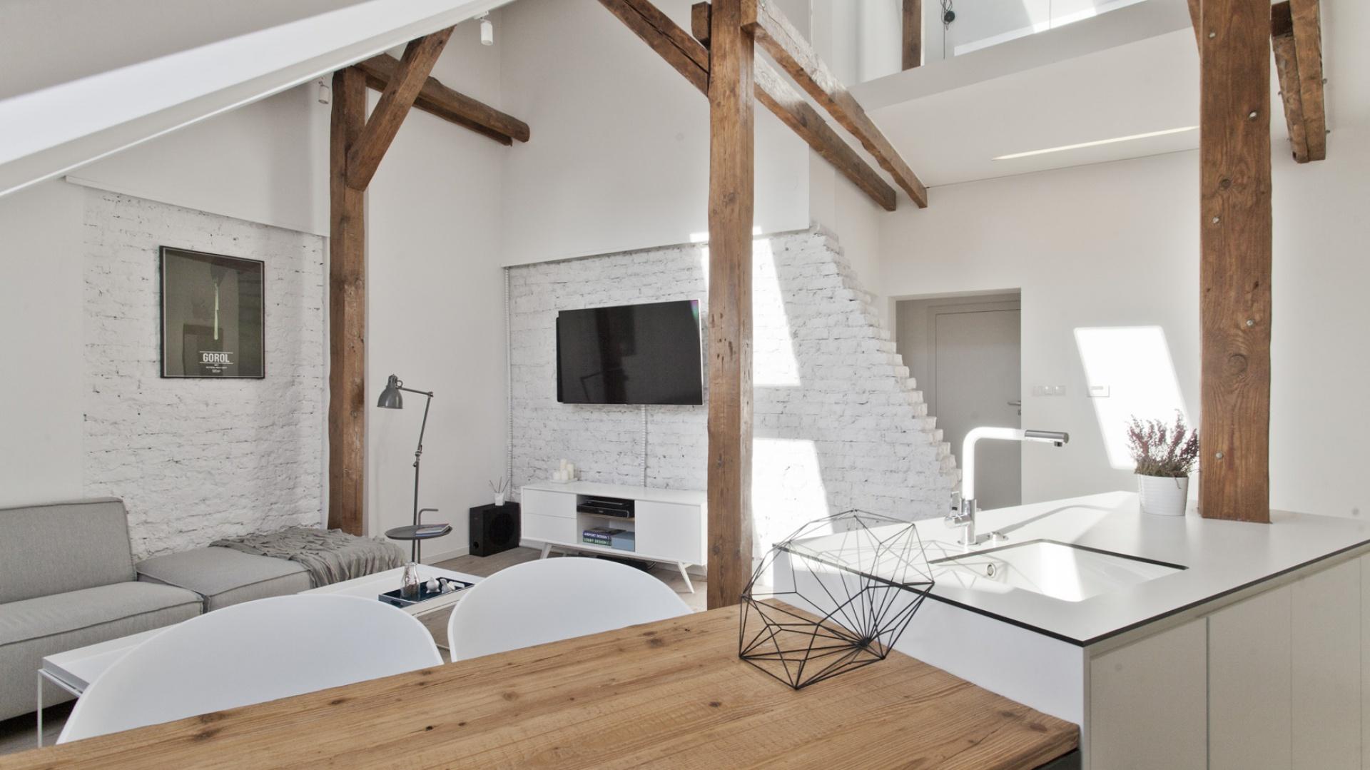 Odsłonięta konstrukcja więźby dachowej stała się integralnym elementem aranżacyjnym wnętrza. Wyeksponowane na tle białych ścian drewniane belki nadają wnętrzu przytulny charakter. Projekt: Superpozycja architekci. Fot. Przemek Skóra.