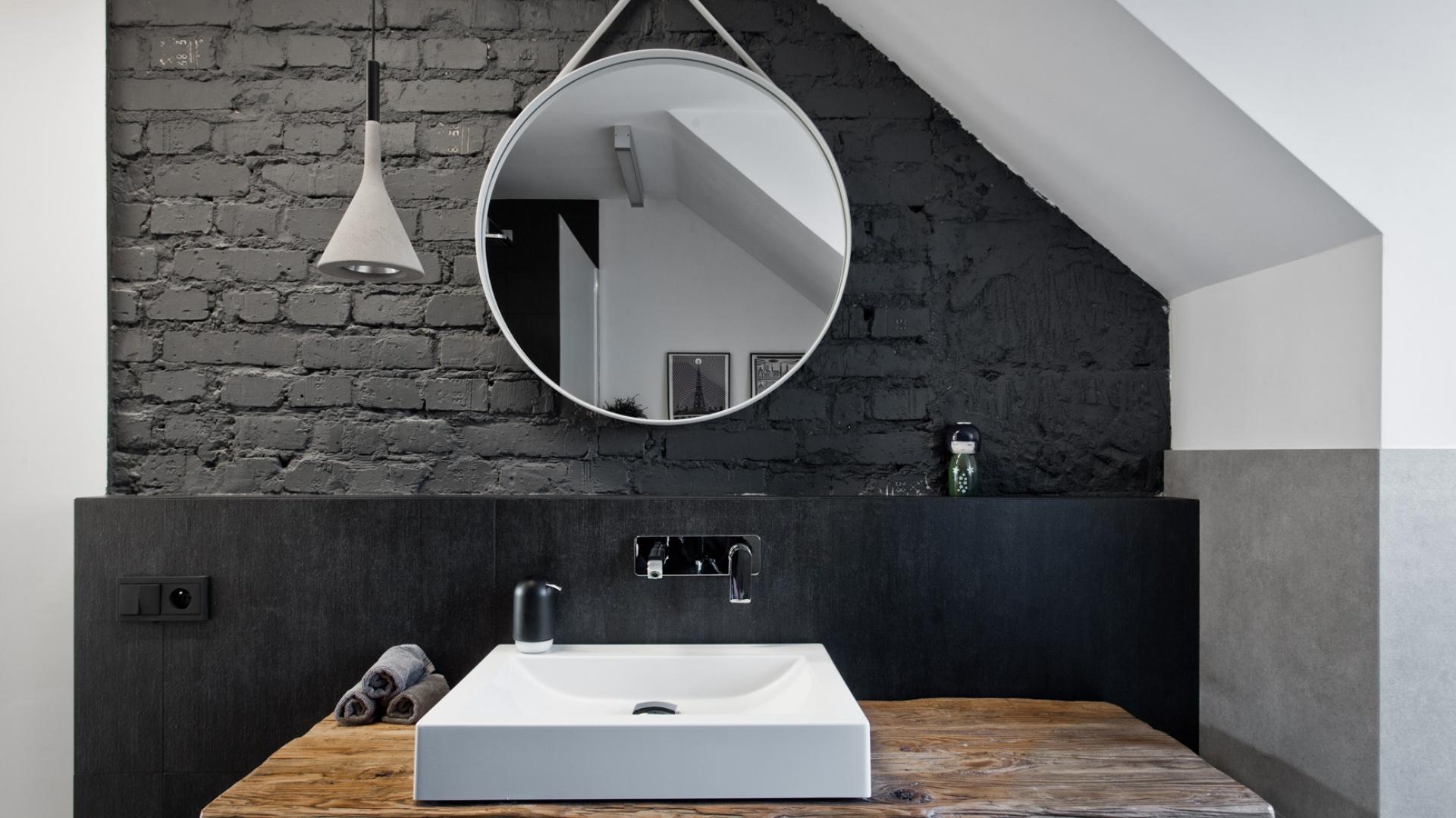 W łazience - podobnie jak w strefie dziennej - odsłonięto starą cegłę. Następnie pomalowano ją na antracytowy kolor. Projekt: Superpozycja architekci. Fot. Przemek Skóra.