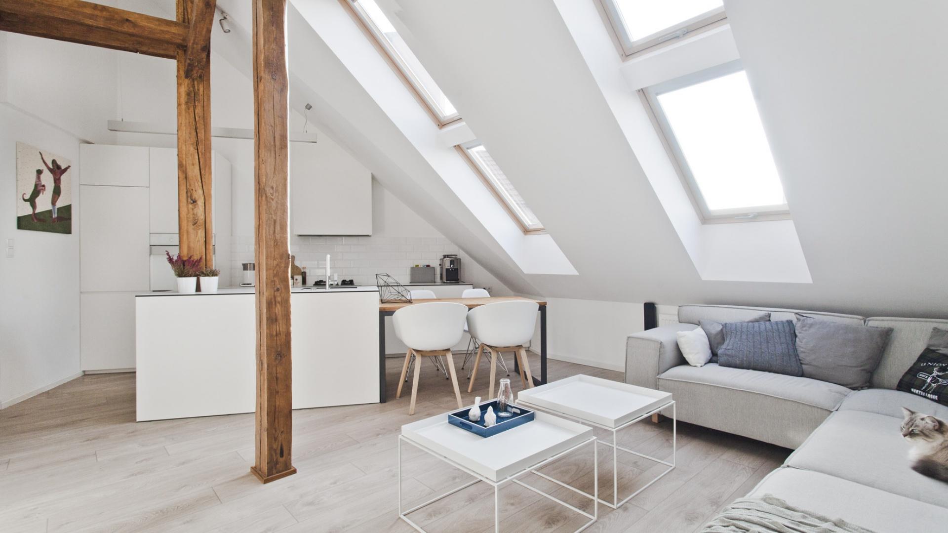 Wnętrze rozświetlają liczne okna połaciowe. Wpadające przez nie światło odbija się od białych ścian i mebli. Projekt: Superpozycja architekci. Fot. Przemek Skóra.
