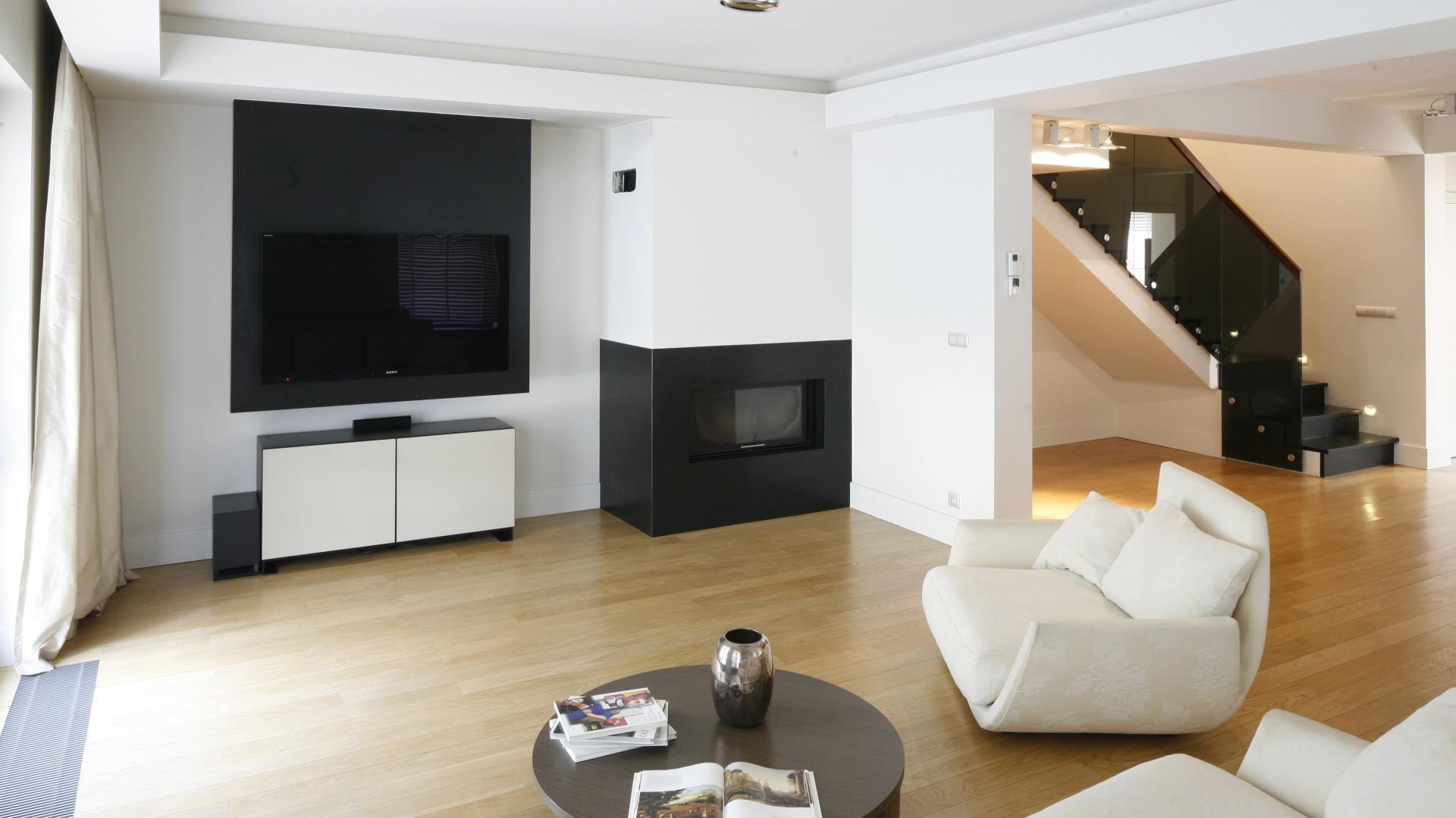 Elegancka przestrzeń dzienna urządzona została minimalistycznie, lecz przytulnie. Ciepłą atmosferę buduje kolorystyka oraz drewniana podłoga. Projekt: Kamila Paszkiewicz. Fot. Bartosz Jarosz.