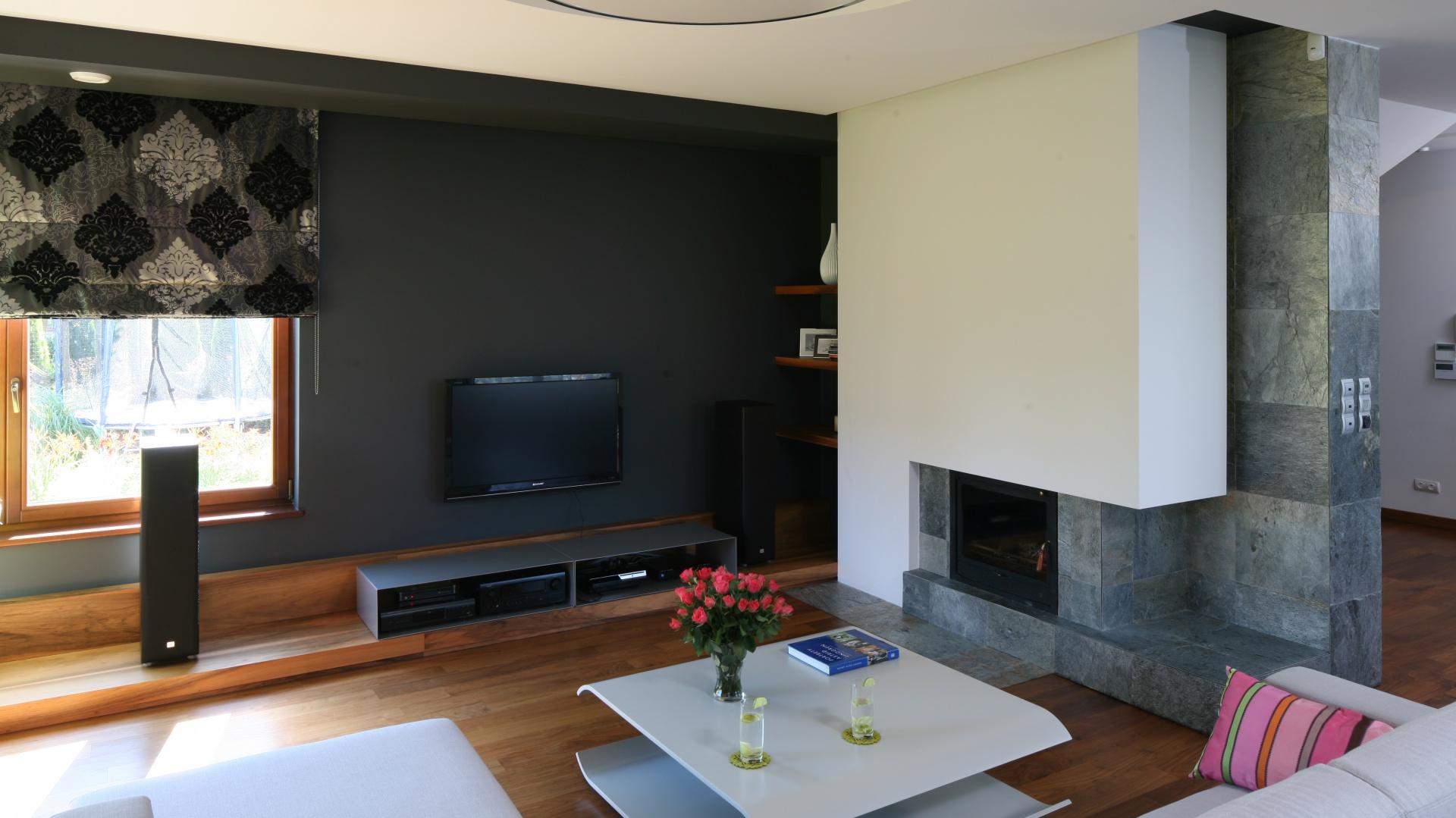 W przestronnym wnętrzu szary kolor ozdobił nie tylko ściany, ale też duży narożnik.Całość ociepla naturalne drewno. Projekt: Magdalena i Maciej Konopko. Fot. Bartosz Jarosz.