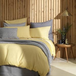 W sypialni warto bawić się barwami, najlepiej tymi stonowanymi. Połączenie szarości i rozbielonej żółcieni nada wnętrzu ciekawy styl. Fot. Secretlinenstore