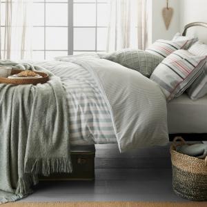 Duża ilość poduszek to podstawa, jeśli chcemy ładnie zaścielić za dnia łóżko. Są one naturalną ozdobą i jednocześnie sprawiają, że cała aranżacja wydaje się bardziej przytulna. Fot. Matalan.