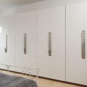 Bardzo pojemna wysoka zabudowa, funkcjonująca jako praktyczna garderoba, pokrywa niemal cała ścianę w sypialni. Długie metalowe uchwyty zdobią białe fronty mebli kuchennych. Projekt: Właściciele. Fot. Bartosz Jarosz.