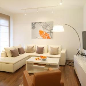 Otwartą strefę dzienną zaaranżowano w kolorze złamanej bieli, którą dodatkowo ociepla drewniana podłoga w salonie. Duża, narożna kanapa organizuje strefę wypoczynkową. Podkreśla ona relaksacyjny charakter całego wnętrza. Projekt: Małgorzata Galewska. Fot. Bartosz Jarosz.