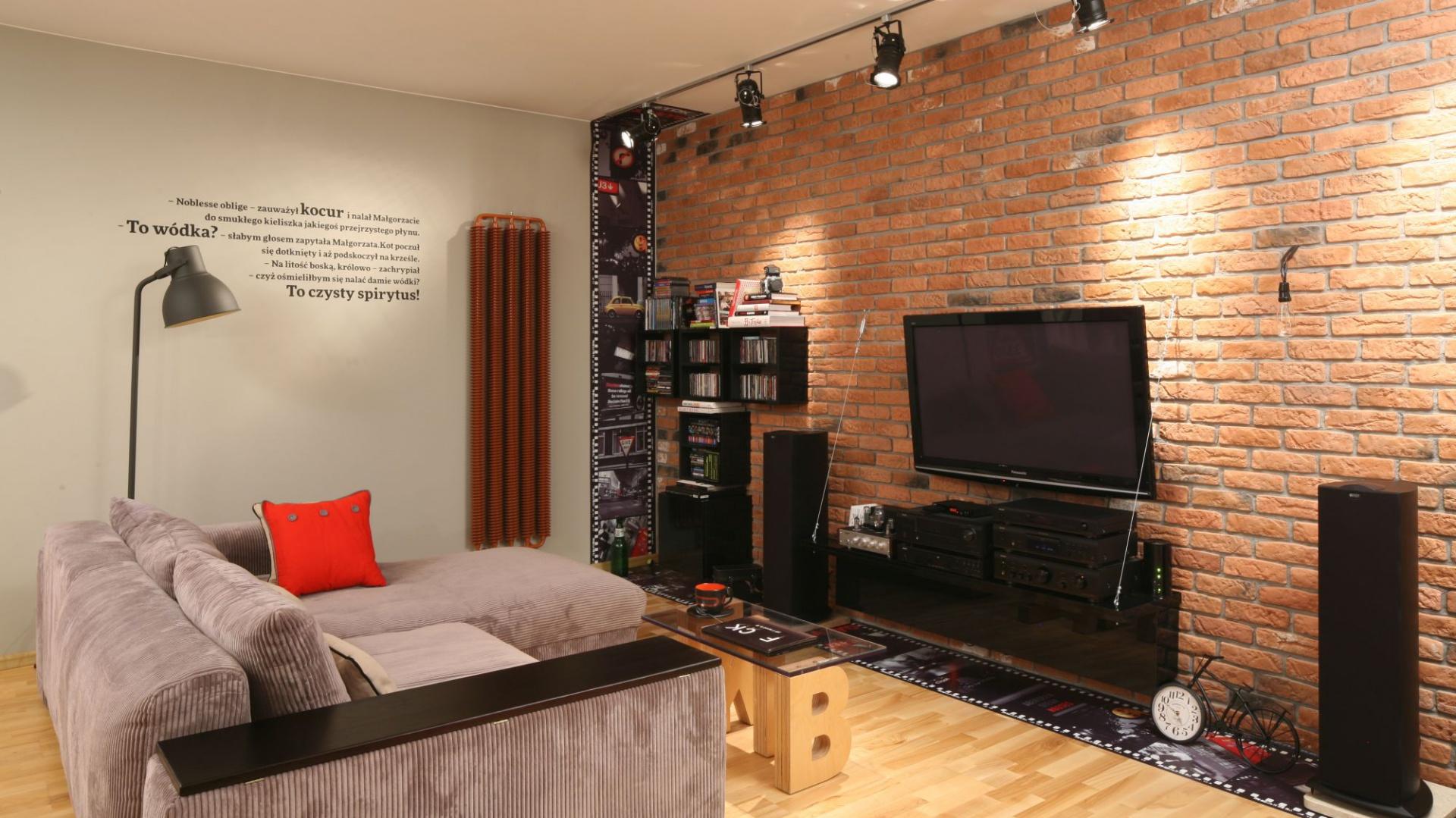 Otwartą strefę dzienną, podobnie jak całe mieszkanie, urządzono w loftowym klimacie. Podkreśla go wyłożona czerwoną cegłą ściana. Projekt: Iza Szewc. Fot. Bartosz Jarosz.
