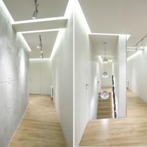 Hol rozświetla nowoczesne oświetlenie, a odrobinę industrialnego szyku wprowadza beton na ścianie. Projekt: Katarzyna Uszok, Natalia Krzymińska. Fot. Bartosz Jarosz.
