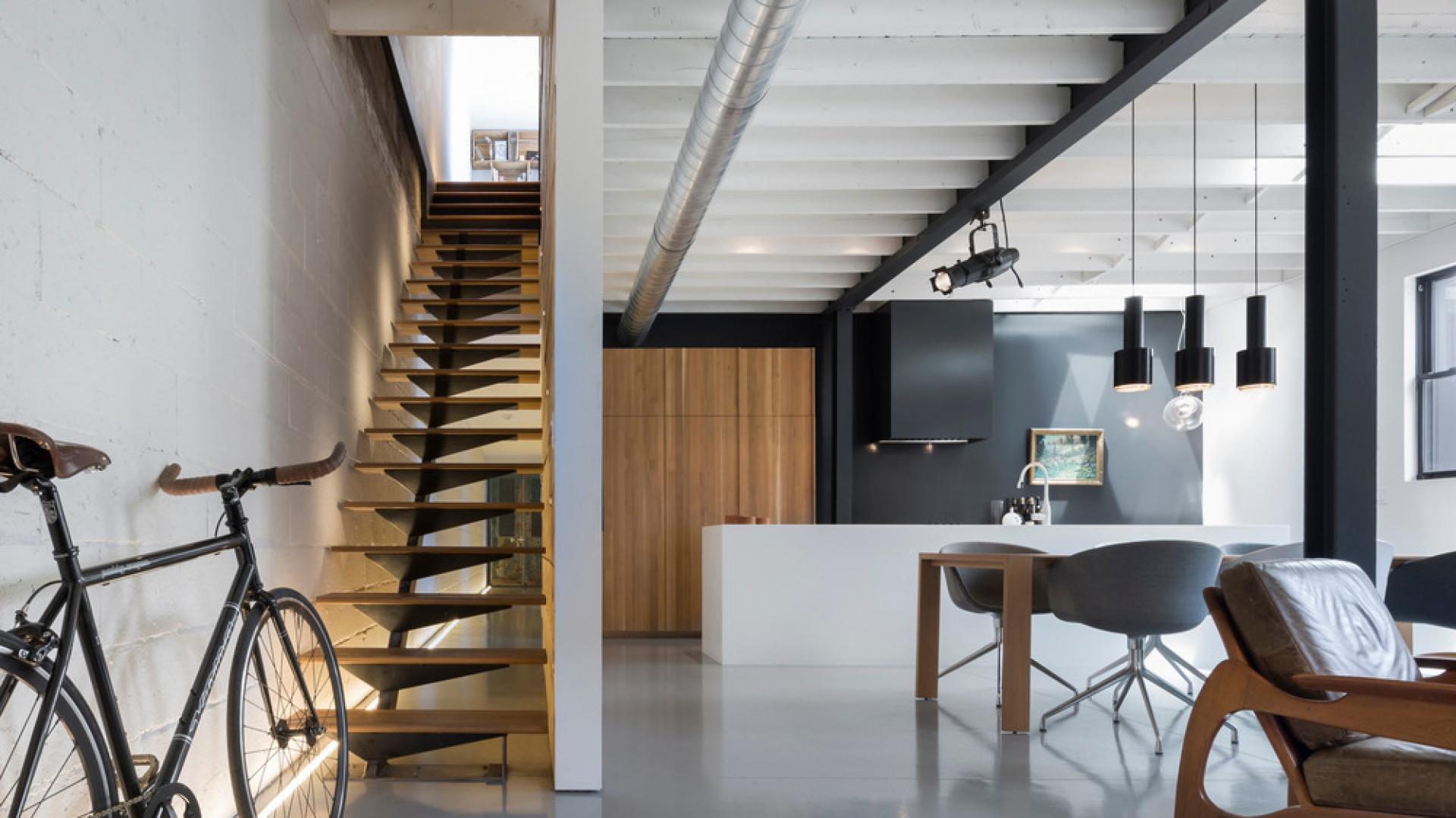 Nowoczesne wnętrze urządzono w stylu soft-loft. Dominują gładkie powierzchnie, minimalizm aranżacyjny oraz loftowe akcenty. Projekt: Atelier Moderno. Fot. Stéphane Groleau.
