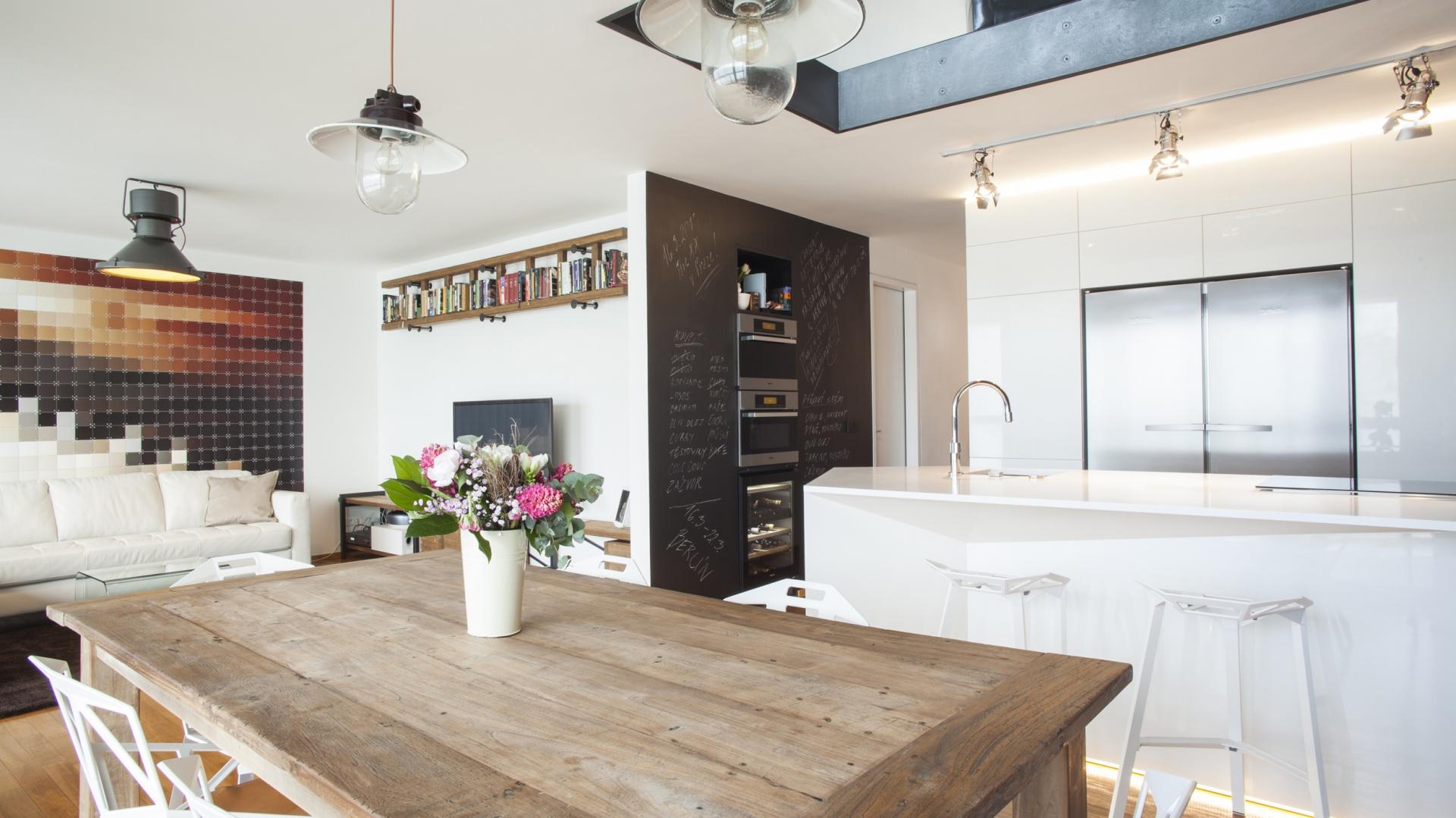 W loftową aranżację idealnie wpisują się lampy nad stołem oraz sam mebel, wykonany z surowego drewna. Projekt: Projekt: B² Architecture. Fot. Michal Šeba.