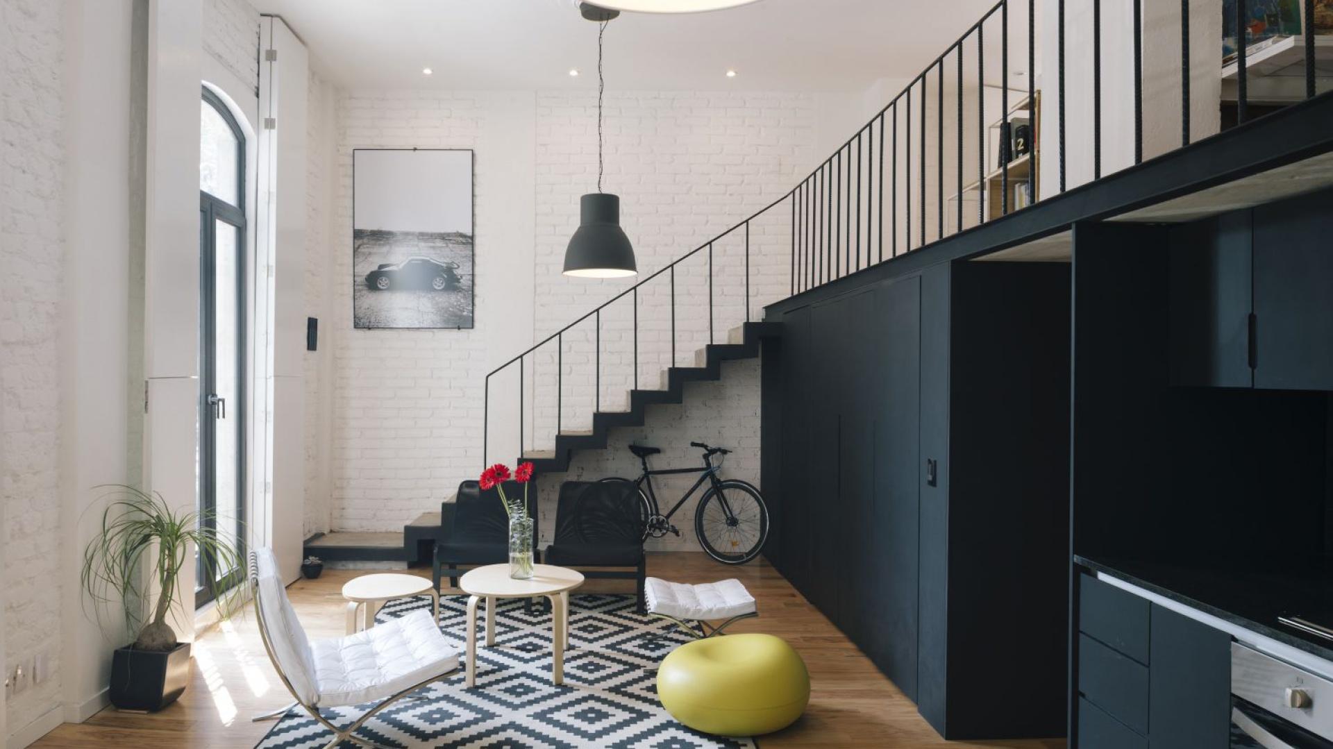 Czarne metalowe schody na tle ściany z pomalowaną na biało cegłą tworzą efektowny kontrast wpisujący się w stylistykę loftową. Projekt: Eduardo Cadaval & Clara Solà-Morales. Fot. Miguel de Guzmán.