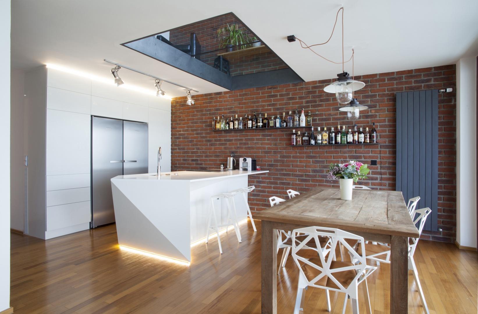 W tym wnętrzu atmosferę loftu buduje przede wszystkim czerwona cegła na ścianie w kuchni oraz towarzyszące jej lampy na odsłoniętych oplotach. Projekt: Projekt: B² Architecture. Fot. Michal Šeba.