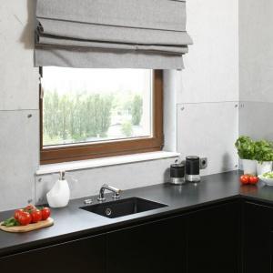 Zabudowa kuchenna w tej kuchni jest bardzo oszczędna stylistycznie. Fronty mebli są gładkie, wykończone czarnym, matowym lakierem. Pod ciemnoszarym blatem podwieszono zlewozmywak w takim samym grafitowym kolorze. Projekt: Małgorzata Łyszczarz. Fot. Bartosz Jarosz.