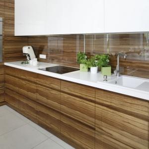 W tej pięknej kuchni fronty mebli i ścianę nad blatem zdobi poziomy dekor drewna podczas gdy blat jest śnieżnobiały. W śnieżną biel wpisuje się zlewozmywak w takim samym kolorze co blat. Projekt: Agnieszka Ludwinowska. Fot. Bartosz Jarosz.