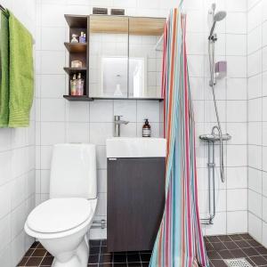 Łazienka to powtórzenie kolorów z kuchni, z przewagą bieli względem grafitowej szarości. Fot. Svenksfast.se.