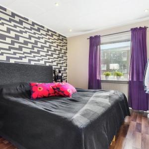 Łóżko z miękkim tapicerowanym zagłówkiem stanęło na tle ściany, którą zdobi opartowski wzór. Fot. Svenksfast.se.