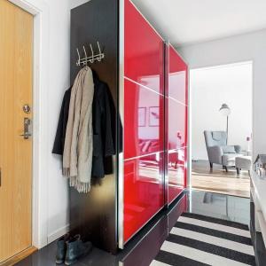 Czerwone fronty zabudowy przyciągają wzrok i stanowią swoisty kierunkowskaz, prowadzący do poszczególnych pomieszczeń. Fot. Svenksfast.se.