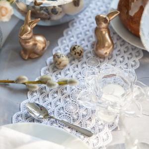 Stół na Wielkanoc można również udekorować w stylu glamour. Kojarzący się ze świętami Bożego Narodzenia zestaw złota i bieli okazuje się pięknie prezentować również w otoczeniu wielkanocnych motywów, jak króliczki i bazie. Fot. Westwing.