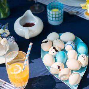 Wielkanocny stół ubrany w błękity będzie prezentował się bardzo wiosennie, a na tle niebieskiego obrusu biała porcelana nabierze marynistycznego wyrazu. Fot. Westwing.