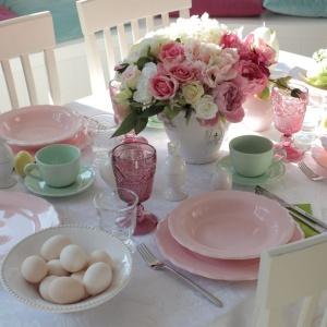 Piękna, romantyczna aranżacja stołu zdominowana została przez pudrowy odcień różu. Jest bardzo delikatnie, kobieco i wiosennie. Fot. Tendom.pl.