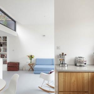 Jasne, przestronne wnętrze ocieplają drewniane akcenty, np. w formie frontów zabudowy kuchennej. Projekt: Scenario Architecture. Fot. Matt Clayton.