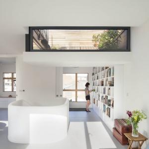 Jedną ze ścian w otwartej strefie dziennej w całości przeznaczono na biblioteczkę. Projekt: Scenario Architecture. Fot. Matt Clayton.