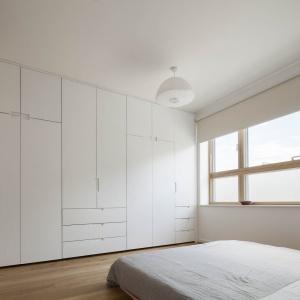 W sypialni zaprojektowano pojemną zabudowę na całą ścianę, pełną mniejszych i większych szaf i szuflad. Projekt: Scenario Architecture. Fot. Matt Clayton.