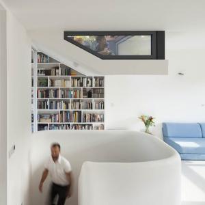 Klatkę schodową, otwierającą się bezpośrednio na otwartą strefę dzienną, otula ciekawie wyprofilowany biały murek. Projekt: Scenario Architecture. Fot. Matt Clayton.