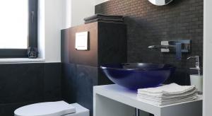 Ta mała toaleta dla gości znajduje się na parterze domu. Jej ściany są wykończone pięknym, naturalnym łupkiem. Uwagę zwraca zwraca szklana umywalka w kobaltowym kolorze.