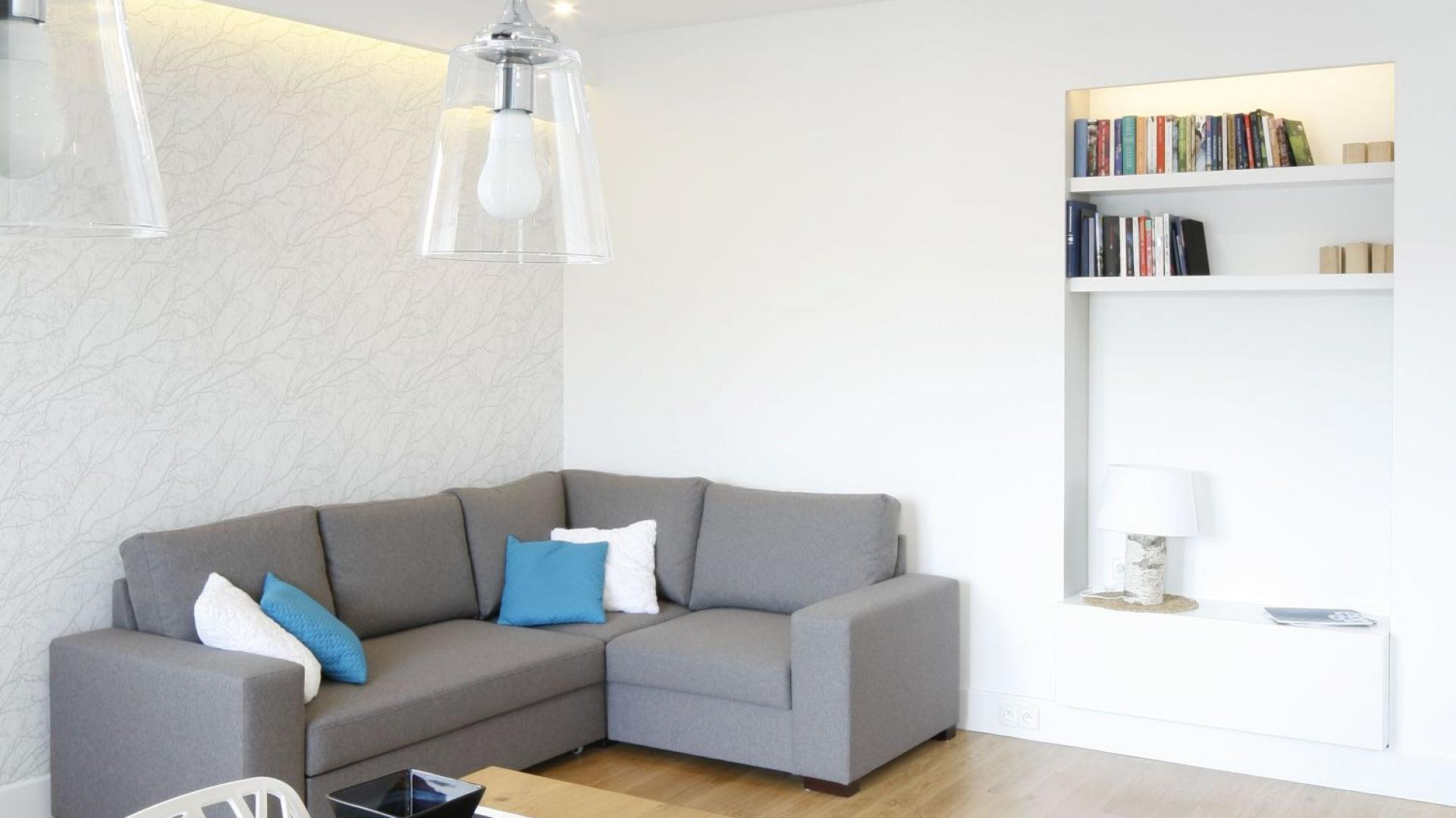 W niewielkim mieszkaniu w bloku strefę wypoczynku stanowi niewielki narożnik w szarym kolorze ustawiony na tle białych ścian. Projekt: Agnieszka Zaremba i Magdalena Kostrzewa-Świątek. Fot. Bartosz Jarosz.