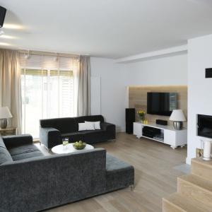 Miękki narożnik i dwuosobowa sofa zachęcają do wypoczynku w tym szaro-beżowym salonie. Projekt: Małgorzata Galewska. Fot. Bartosz Jarosz.