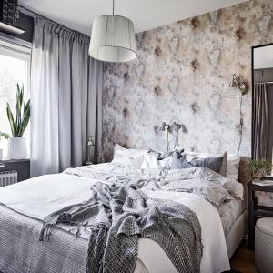 W jednej z sypialni na ścianie położono wzorzystą tapetę z interesującym efektem wypłowiałego, postarzanego materiału. Fot. Janne Olander/Stadshem.se.