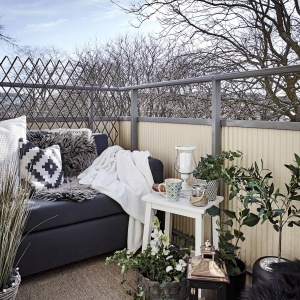 Balkon to prawdziwy zakątek relaksu. Znalazł się tutaj niewielki stolik oraz wygodne siedzisko, któremu przytulność nadają koce i pledy. Fot. Janne Olander/Stadshem.se.