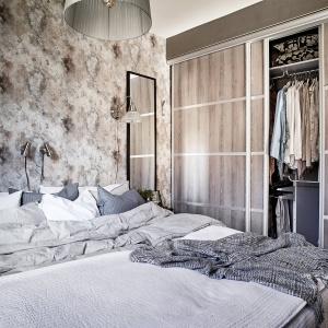 W sypialni znalazło się również miejsce na pojemną garderobę za frontami wysokiej zabudowy, które zdobi drewniany dekor. Fot. Janne Olander/Stadshem.se