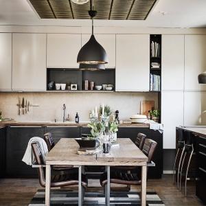 Kuchnię otwarto na salon, a pomiędzy pomieszczeniami ustawiono stół z blatem z postarzanego drewna. Fot. Janne Olander/Stadshem.se.