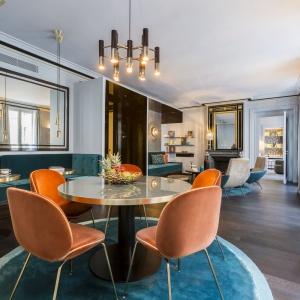 Cechą charakterystyczną projektów Gerard Faivre są materiały najwyższej jakości oraz designerskie dodatki i meble. Tutaj nad stołem zawisła lampa marki Delightful - znanego producenta designerskiego oświetlenia. Projekt: Gerard Faivre Paris.