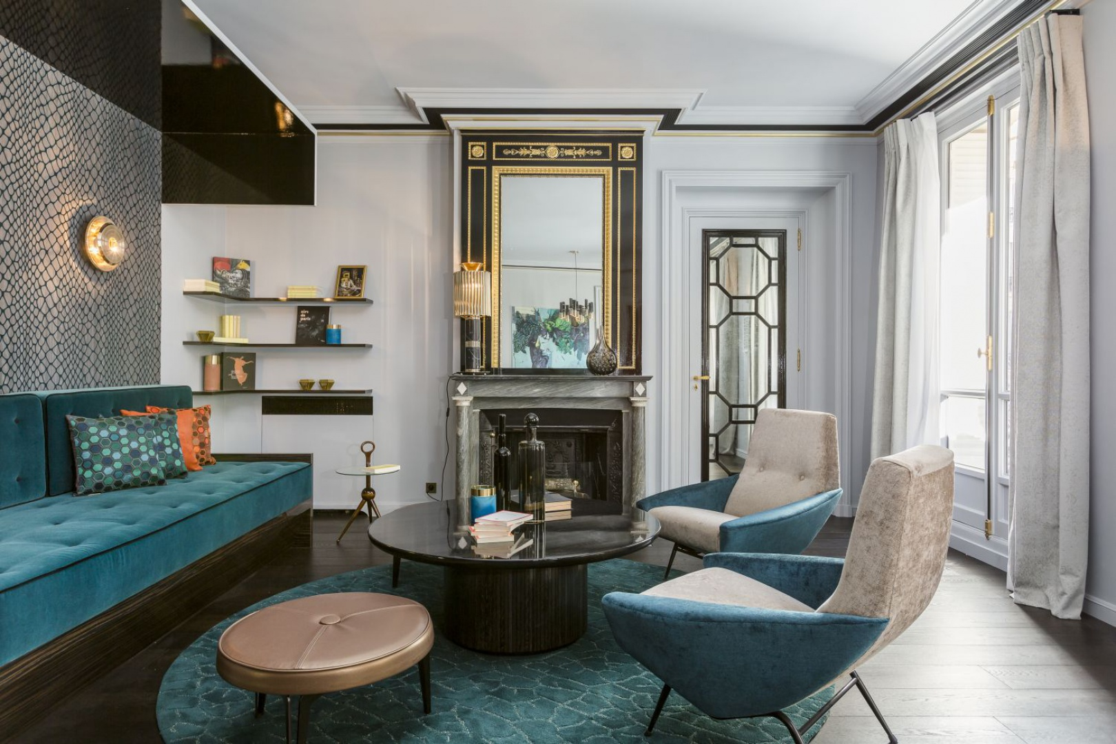 W salonie wzrok przyciąga kominek z lustrem w pięknej, czarno-złotej ramie nad paleniskiem.  Projekt: Gerard Faivre Paris.