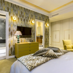 Wysoka zabudowa poprowadzona wzdłuż całej ściany zachwyca zdobieniami w złotym kolorze. Vintage'owy fotel i wzorzysta tapeta na ścianie nadają wnętrzu charakter. Projekt: Gerard Faivre Paris.