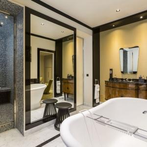 W łazience, bezpośrednio połączonej z sypialnią wprowadzono biel, która odciąża wizualnie mocne, drewniane akcenty. Projekt: Gerard Faivre Paris.