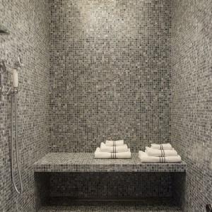 Oprócz wolno stojącej wanny, domownicy bądź goście mają do dyspozycji również przestronną strefę prysznica wyłożoną drobną mozaiką. Projekt: Gerard Faivre Paris.