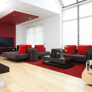 Ścianę za telewizorem wyeksponowano mocnym czerwonym kolorem, pokrywającym zabudowę g-k, która przechodzi efektownie w podwieszany sufit. Projekt: Michał Mikołajczak. Fot. Bartosz Jarosz