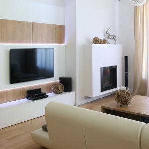 Dwa drewniane panele oraz asymetrycznie usytuowany w stosunku do nich biały panel stanowią nowoczesne i eleganckie tło dla telewizora. Dodatkowy efekt tworzy oświetlenie pod białym panelem. Projekt: Małgorzata Błaszczak. Fot. Bartosz Jarosz