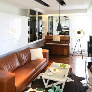 Lustro na ścianie nad pianinem, chociaż niewielkie pokazuje znajdującą się naprzeciw kuchnię i dodaje salonowi przestrzeni. Projekt: Małgorzata Mazur. Fot. Bartosz Jarosz